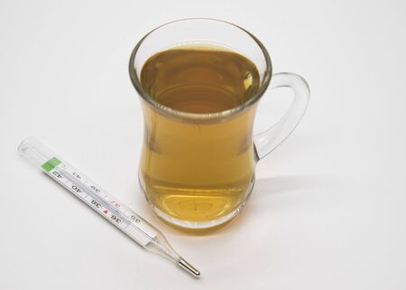 Transparent Cup with herbal tea and thermometer on a light background. Banco de Imagens - 133626661