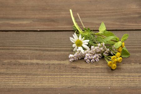Bouquet of fresh spicy herbs and medical herbs on a on wooden background Banco de Imagens - 133626663