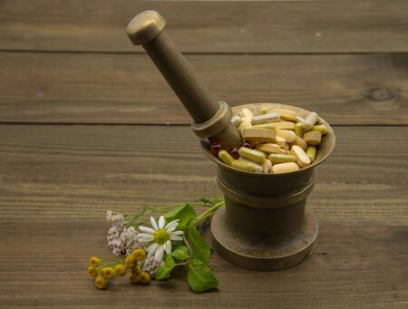 A copper mortar full of capsules and pills. Nearby lie medicinal flowers.On a wooden background.