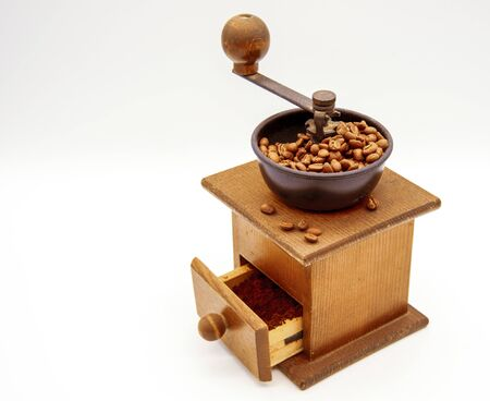 Wooden hand grinder in retro style with coffee beans on a light background.