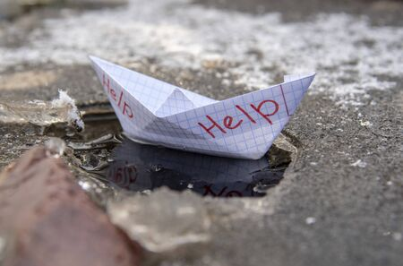 A paper boat made of a checkered notebook with the inscription help stuck in the ice.