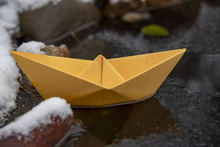 Yellow bright paper boat stuck in the ice, on a frozen puddle.