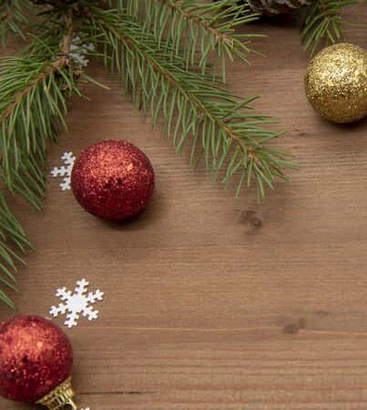 Fir branches,Christmas balls and white snowflakes on a wooden background.Christmas background, top view, Flatley