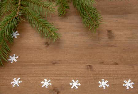 Fir branches and white snowflakes on a wooden background.Christmas background, top view, Flatley