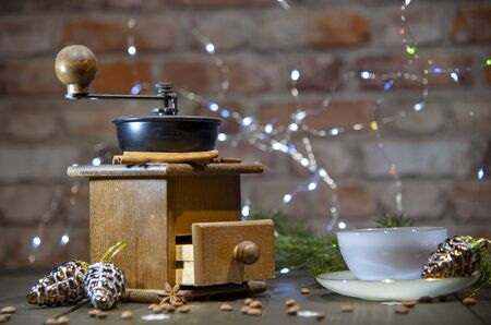 An old hand-held coffee grinder and a porcelain Cup against a brick wall. Decorated with Christmas toys, lanterns and fir branches. New year in loft style.