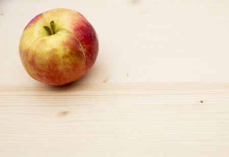 One fresh ripe bright Apple on a light wooden background. Stockfoto
