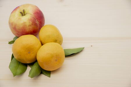 One fresh ripe bright Apple and yellow-green tangerines with leaves on a light wooden background.