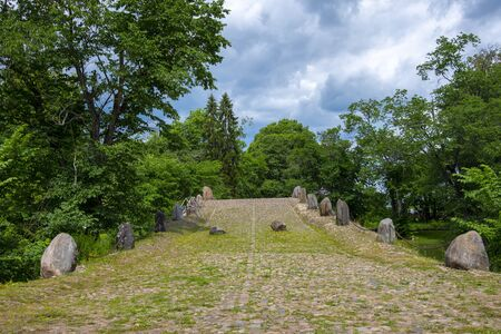 Stone bridge on the background of bright lush green trees and cloudy sky. Summertime. Reklamní fotografie - 133846101