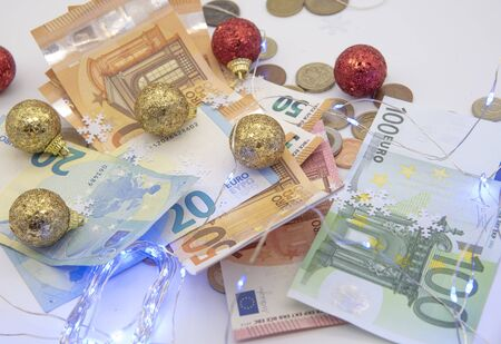 Euro bills and different coins with Christmas decoration on a light background.