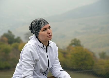 A woman in a bandana and a white hoodie sits on a wooden bench against a blurred misty autumn landscape.