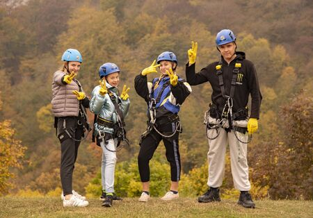 Armenia, enokavan, October 2019. Four teenagers in zipline equipment pose merrily against the backdrop of the autumn forest. Series of photographs.