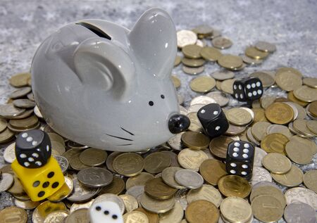 On a gray background mouse-piggy Bank on a pile of coins and attributes of gambling.
