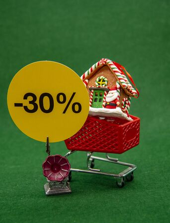 Shopping cart with a Christmas house and a sign with interest on discounts on a green background.