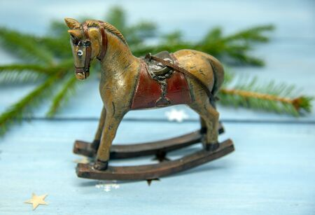 Christmas toy rocking horse and spruce branches on a blue wooden background.