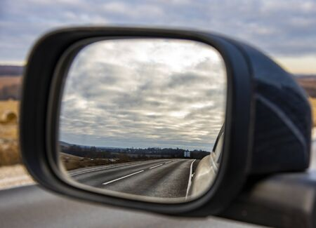 The road and the cloudy sky are reflected in the mirror of the car.