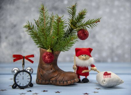 Fir branches in a clay Shoe, Christmas decor, Santa Claus and an alarm clock on a blue wooden background.