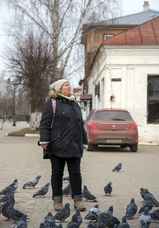 Russia, Yuriev-Polsky, November 2019. A woman stands in the town square surrounded by pigeons.