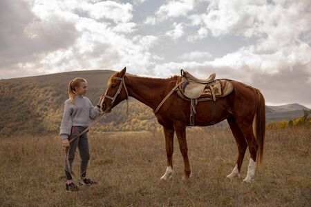 Armenia, Lori region, October 2019. A teenage girl stands in a field with a horse and holds it with one hand under the bridle, and the second strokes the muzzle.