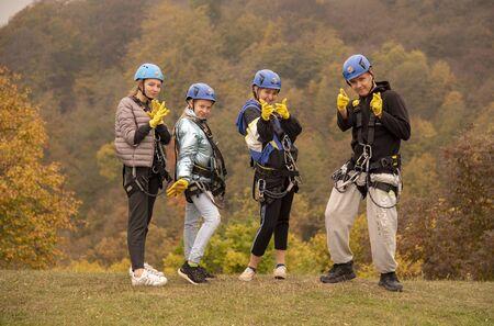 Armenia, enokavan, October 2019. Four teenagers in zipline equipment pose merrily against the backdrop of the autumn forest. Series of photographs.