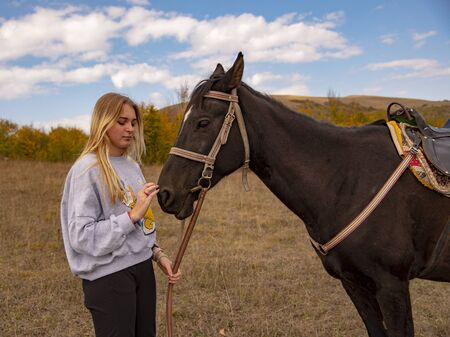 A young girl with blond hair gently strokes the brown horse