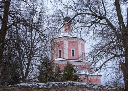 Pink restored church on a background of a gloomy winter sky.