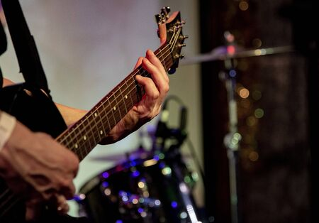 Russia, Moscow, 06 December 2019. Concert of a rock band in a bar. Guitar neck and male hands. Editorial
