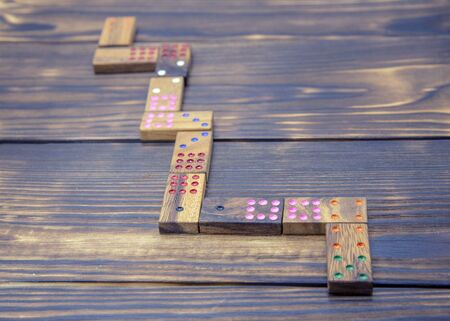 Playing dominoes on a wooden table. Dominoes game concept.