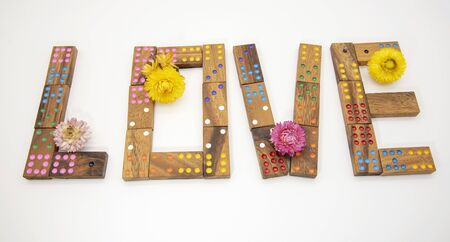 The word love, made of wooden dominoes and decorated with dry flowers on a light background.