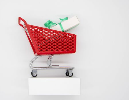 Shopping cart with box, on a stand, on a light background.