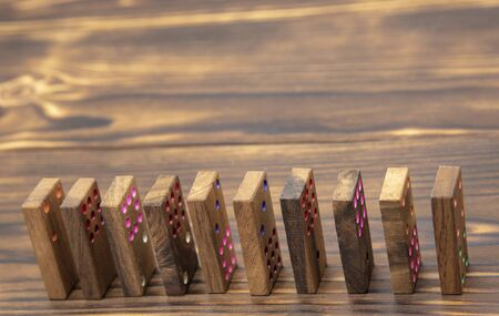 Domino chips placed on edge one after the other on a wooden textured table.