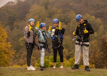 Armenia, enokavan, October 2019. Series of photographs. Group of people in zipline equipment pose merrily against the backdrop of the autumn forest. Editorial