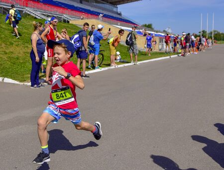 Russia, Moscow, August 2018. Marathon in Krylatskoye.The child joined the male marathoners on the treadmill.