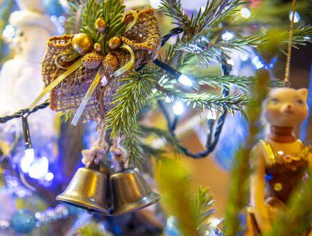 Christmas bright toys and light garlands hang on the Christmas tree.