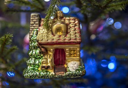 A glass toy house hangs on a Christmas tree on a blurred background of blue lights.