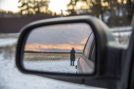 A woman's figure is reflected in the car mirror against the background of a sunset on a winter evening.