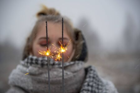 Cheerful burning sparklers on the background of a blurred portrait of a girl in nature. Imagens