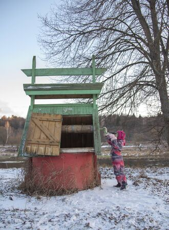 A little girl turns the handle of a village well on a winter day.