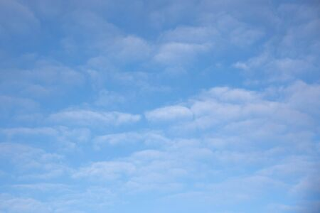Bright blue winter sky with thick white clouds.