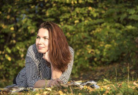 A middle-aged woman lies on a tartan blanket in an autumn Park.