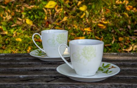 Two cups of tea stand on a wooden surface, against the background of autumn leaves.