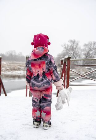 A little girl is standing in the snow with her back to the camera with a toy in her hand on a blurred natural background.