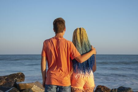 Two teenagers embracing stand with his back to the camera and look at the waves crashing on the rocks.The spray flies in all directions.The girl with the blue Senegalese braids. Banco de Imagens