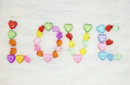 The word love is made up of colored glass stones on a light background.