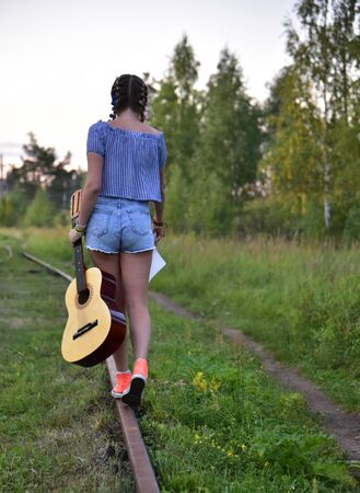A teenage girl in a striped t-shirt with a guitar walks along the rails into the distance. Banco de Imagens