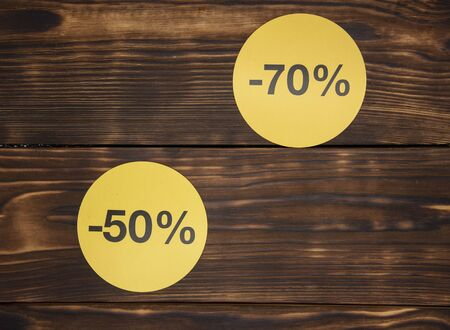 Yellow round signs with discount percentages on a dark wooden background.