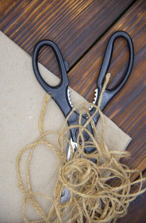 Tools for crafts on a wooden table top. Scissors, coarse thread and craft paper.