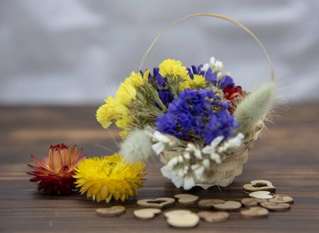 Basket with dried flowers and wooden hearts around on a wooden table top. Banco de Imagens