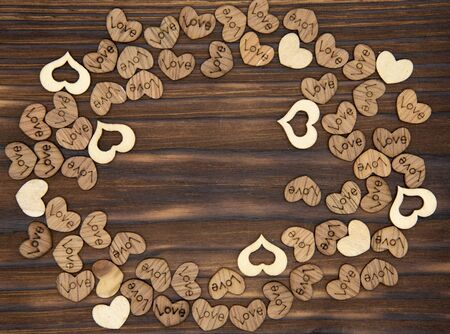 A frame of many wooden hearts on a dark wooden background. Top view, copy space Banco de Imagens