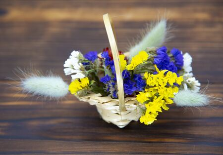 Wicker basket with bright dried flowers on a dark wooden background. Banco de Imagens