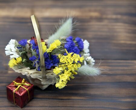 A wicker basket with bright dried flowers and a red gift box on a dark wooden background. Banco de Imagens